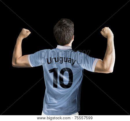 Uruguayan soccer player celebrates on black background