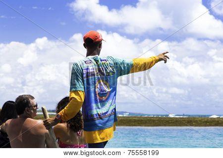 RECIFE, BRAZIL - CIRCA JAN 2014 - Unidentified Guide show to the tourists the Barrier reef in Porto de Galinhas, Recife, Pernambuco - Brazil