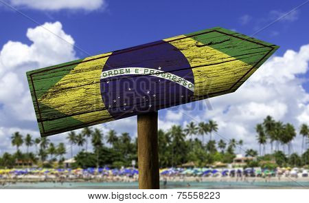 Brazil flag wooden sign on the beach background