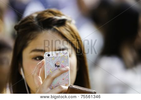 TOKYO, JAPAN - CIRCA MAY 2014: Unidentified Japanese woman uses her device on Shibuya area. Japan has been one of the most advanced countries in the mobile broadband services
