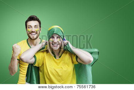 Brazilian couple fan celebrate on green background