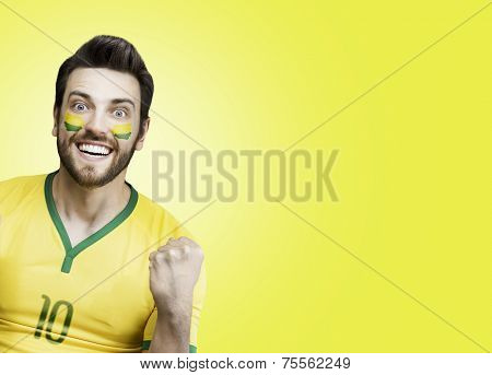 Brazilian soccer fan celebrates on yellow background