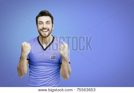 Uruguayan soccer player celebrates on blue background