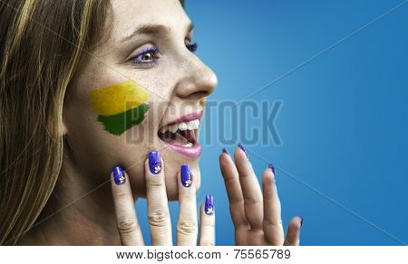 Blonde Brazilian fan celebrates on blue background