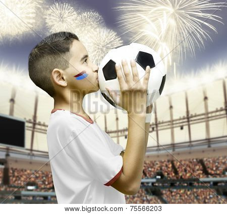 American little boy kissing a soccer ball in the stadium