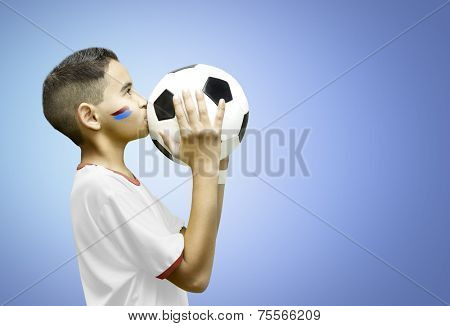 American little boy kissing a soccer ball on blue background