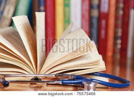 A stethoscope is lying with a book on the desk against books