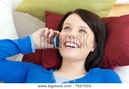 Happy Teen Girl Talking On Phone Lying On A Sofa