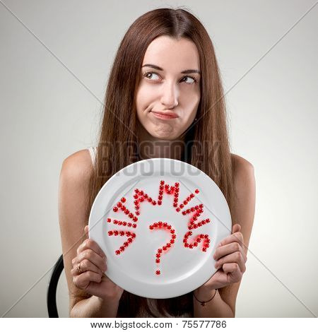 Young woman showing plate with vitamins