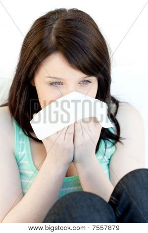 Sick Charming Woman Blowing Sitting On A Sofa