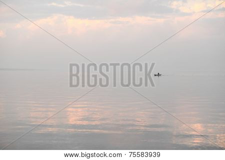 silhouette of a fishing boat on the horizon