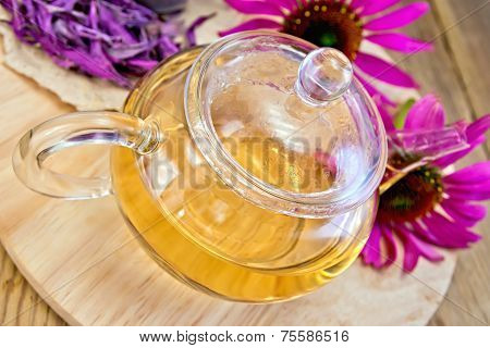 Tea from Echinacea in glass teapot on board