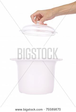 Hand open glass cover of ceramic steam pot on white background.