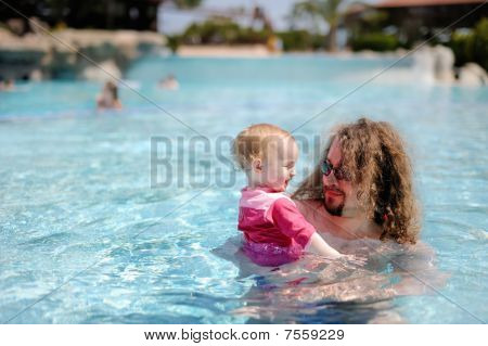 Young Father And His Baby Girl In A Pool