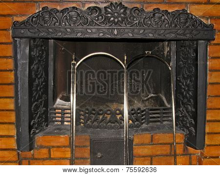 Metal Fireplace With Iron Grate In Masonry