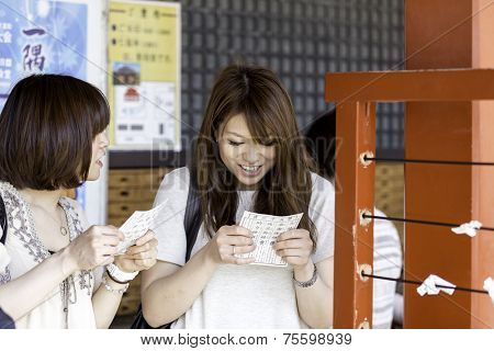 TOKYO, JAPAN - CIRCA MAY 2014: Japanese girl smiles looking at her Omikuju charms at the Asakusa, Tokyo, Japan