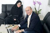 stock photo of hijabs  - Senior Businessman working with Arabian Businesswoman wearing hijab - JPG
