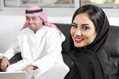 stock photo of hijabs  - Arabian Businesswoman wearing hijab with her boss in background - JPG