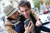 stock photo of cheers  - Cheerful couple having fun playing with smartphone - JPG