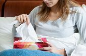 foto of tissue box  - Sick woman lying with box of tissues - JPG