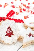 picture of linzer  - Christmas Tree Linzer cookie with powdered icing sugar and red decorations in the background - JPG