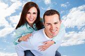 image of piggyback ride  - Portrait of happy man giving piggyback ride to girlfriend against sky  - JPG