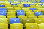 stock photo of bleachers  - Colored Seating rows in a Maracana stadium with weathered chairs - JPG