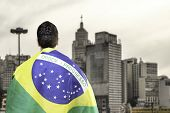 picture of glorious  - Brazilian holding a brazilian flag looks to Sao Paulo Skyline - JPG