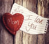 picture of sweethearts  - I Love You Mom written on a peace of paper and a heart on a wooden background - JPG