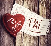 "stock photo of miss you  - ""Te Amo, Pai"" (In portuguese - Love You, Dad) written on a peace of paper and a heart on a wooden background - JPG"