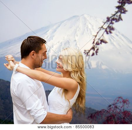 travel, tourism, honeymoon, people and love concept - happy couple hugging over japan mountains background