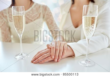 people, homosexuality, same-sex marriage, celebration and love concept - close up of happy married lesbian couple hands on top and champagne glasses over holiday lights background