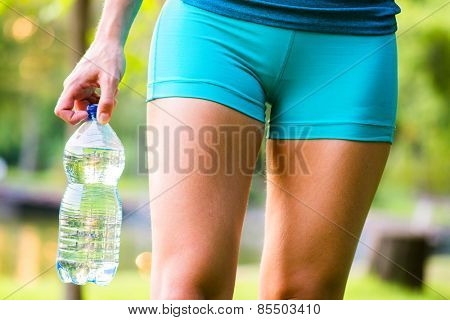 Sporty woman holding bottled water after exercising
