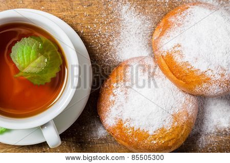 Tea cup with two sugar powdered buns