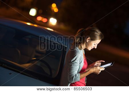 Pretty, female driver using her tablet computer (shallow DOF; color toned image)