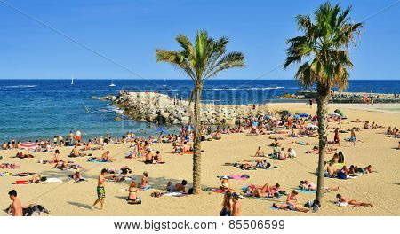 BARCELONA, SPAIN - AUGUST 19: Bathers in La Barceloneta Beach on August 19, 2014 in Barcelona, Spain. This popular beach hosts about 500,000 visitors from everywhere during the summer season