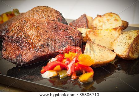 Succulent Thick Juicy Portions Of Grilled Fillet Steak Served With Roasted Potatoes And Peppers On B