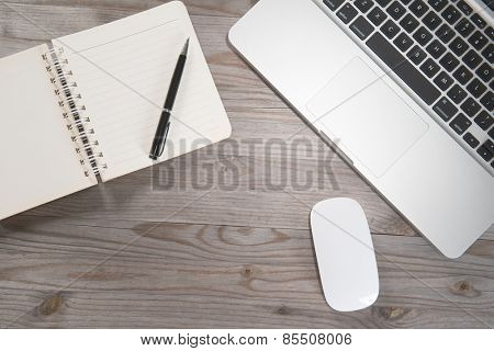 Old wooden office table with notepad, laptop and mouse. View from above with copy space.