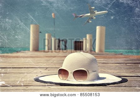 Scrated film look. Hat and sunglasses on the wooden jetty. Exuma, Bahamas