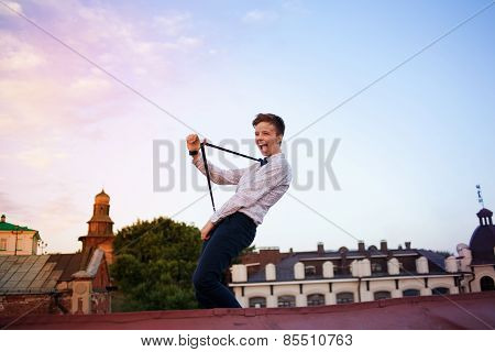 Young Bold Girl Woman Hipster On Roof Showing Off Tongue And Streching Suspenders