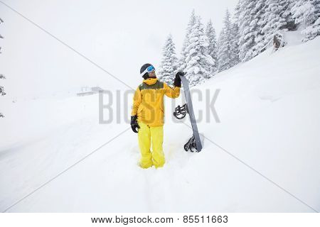 Male snowboarder in yellow sportswear standing with snowboard looking up and planning the route of descent for unknown ski track