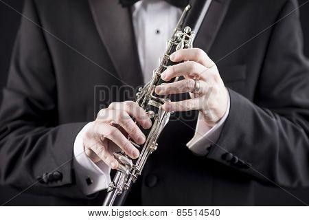 man in tuxedo holding clarinet, closeup