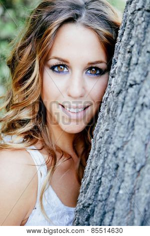 Pretty cool woman leaning on a tree trunk with a beautiful smile