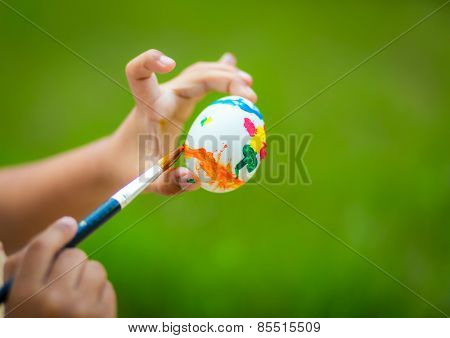 Child hand painting easter egg with paintbrush