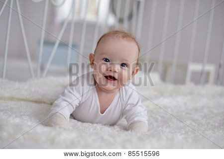Portrait Of A Crawling Baby On The Carpet In Room