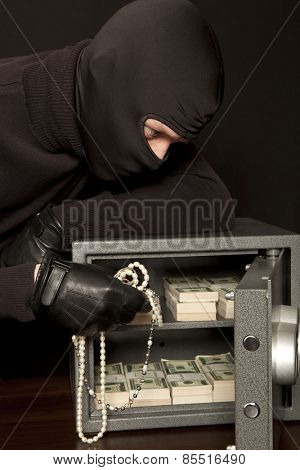 Thief burglar stealing dollar money during home safe code breaking