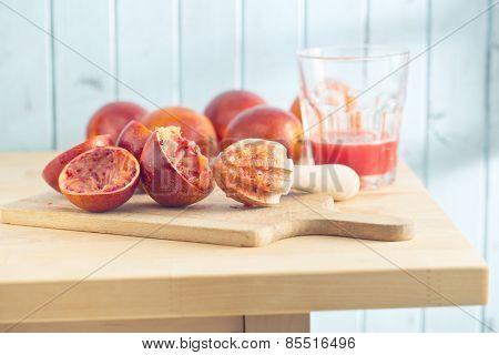 halved blood orange and juicer on kitchen table