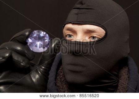 Thief. Man in black mask with a big diamond.Focus on thief