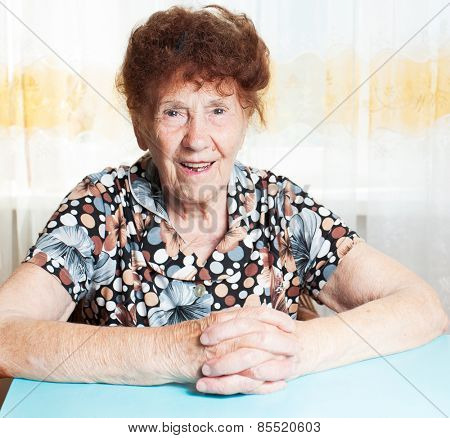 Old woman. Elderly smiling female at home