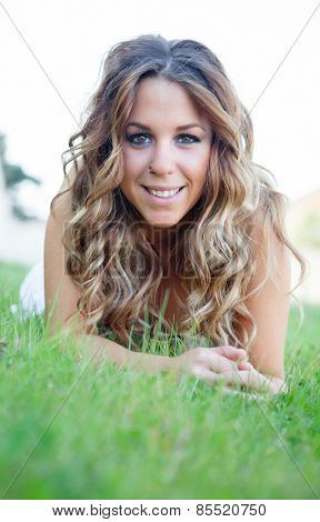 Cool pretty lying girl on the grass with a beautiful smile